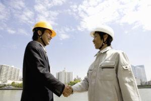 握手する修繕委員長と施工会社